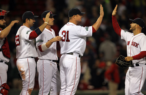 Red Sox starting pitcher Jon Lester celebrates with teamates after throwing a complete game victory. Cody Ross at right.