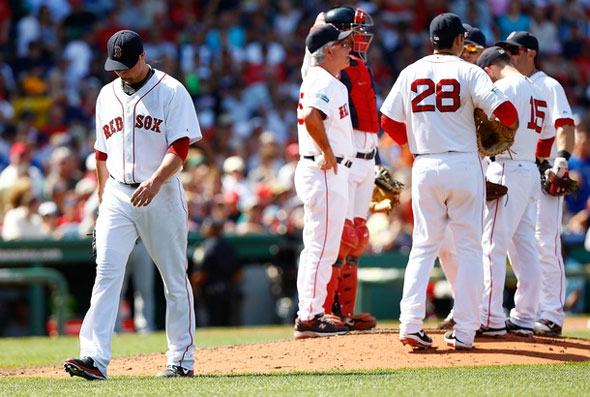Jon Lester of the Boston Red Sox walks to the dugout after being pulled by manager Bobby Valentine #25 in the fifth inning against the Toronto Blue Jays during the game on July 22, 2012 at Fenway Park in Boston