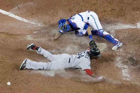 Boston Red Sox's Darnell McDonald slides into home plate to score against Toronto Blue Jays catcher J.P Arencibia during the ninth inning of a baseball game in Toronto on Monday, April 9, 2012. Boston won 4-2.