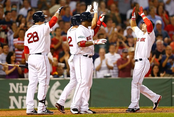 Cody Ross of the Boston Red Sox is congratulated by teammate at home plate after hitting a three run home run against the Chicago White Sox during the game on July 18, 2012 at Fenway Park in Boston, Massachusetts.