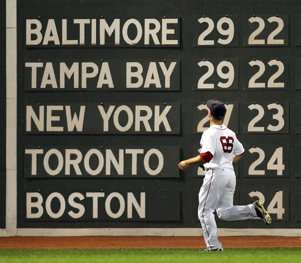 Red Sox left fielder Daniel Nava watches an 8th inning homer by Tigers Delmon Young, as the standing are seen on the scoreboard.