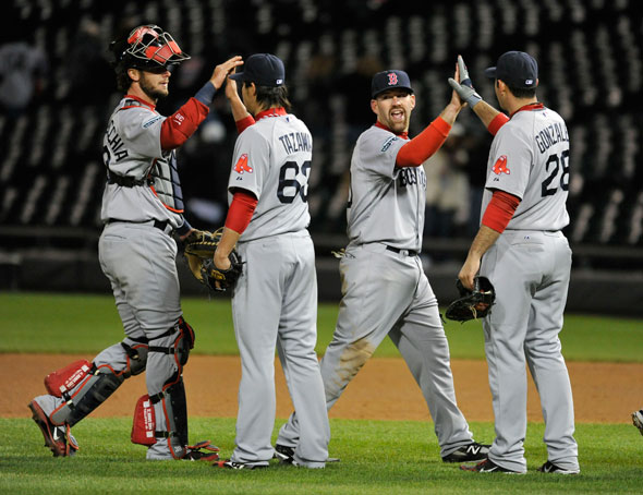 Jarrod Saltalamacchia, Junichi Tazawa, Kevin Youkilis and Adrian Gonzalez of the Boston Red Sox celebrate their win over the Chicago White Sox at U.S. Cellular Field on April 26, 2012 in Chicago, Illinois. The Red Sox defeated the White Sox 10-3.