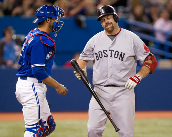 Boston Red Sox Kevin Youkilis, right, reacts in front of Toronto Blue Jays catcher J.P. Arencibia after striking out during ninth inning of a baseball game in Toronto on Wednesday, April 11, 2012.