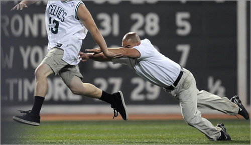 A fan running on the field avoids getting tackled during the eighth inning as the Boston Red Sox take on the Tampa Bay Rays on June 3, 2008 at Fenway Park in Boston, Massachusetts.