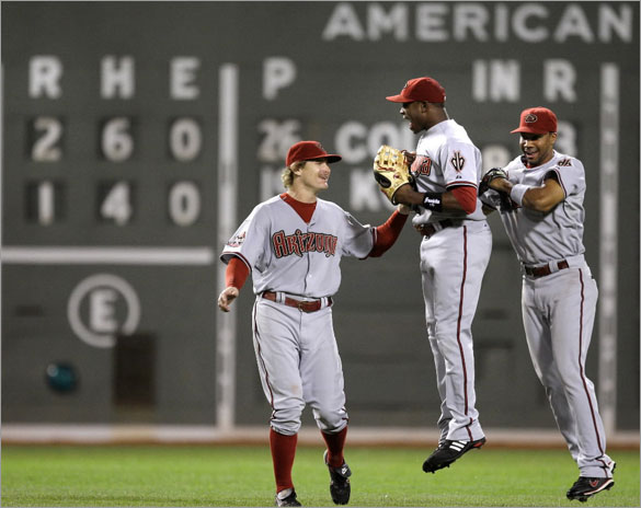 Arizona Diamondbacks rightfielder Justin Upton, center, leaps as he celebrates a 2-1 win over the Boston Red Sox with teammates Eric Byrnes, left, and Chris Young, right, after their MLB baseball game at Fenway Park in Boston, Monday June 23, 2008.