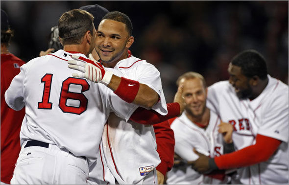 Alex Gonzalez broke an 8-8 bottom of the ninth inning tie with a bases loaded two out single that won the game 9-8. Here he gets a hug at left from teammate George Kottaras, while in the backround right Dustin Pedroia and David Ortiz celebrate together.