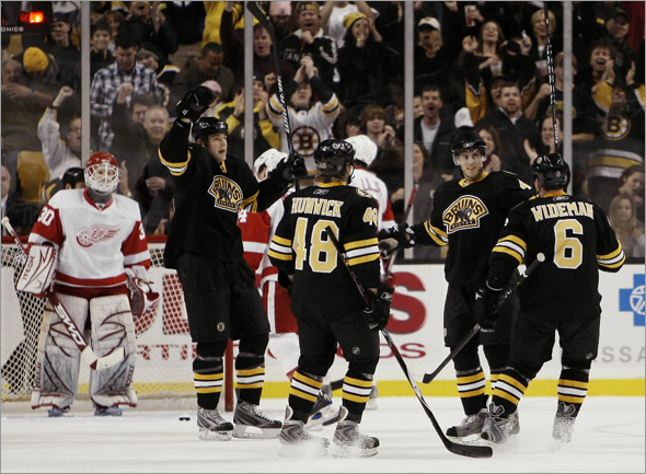 Boston Bruins David Krejci, second from right, of the Czech Republic celebrates his third-period goal with teammates Dennis Wideman (6), Matt Hunwick (48), and Blake Wheeler as Detroit Red Wings goalie Chris Osgood, left, looks on during the Bruins 4-1 win in a hockey game in Boston Saturday, Nov. 29, 2008.