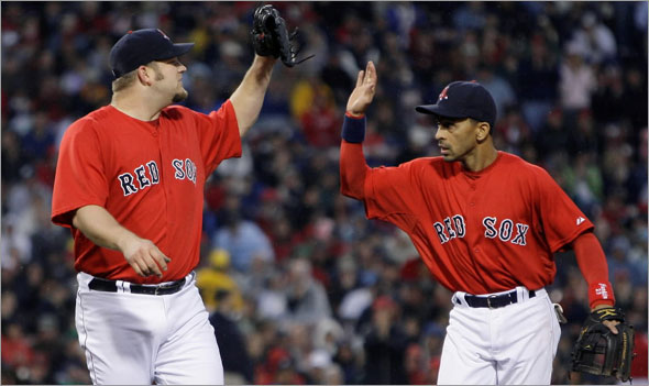 Sox starter Brad Penny, left, high-fives shortstop Julio Lugo after a line out by Texas Rangers Hank Blalock in the fourth inning of a baseball game at Fenway Park in Boston, Friday June 5, 2009.