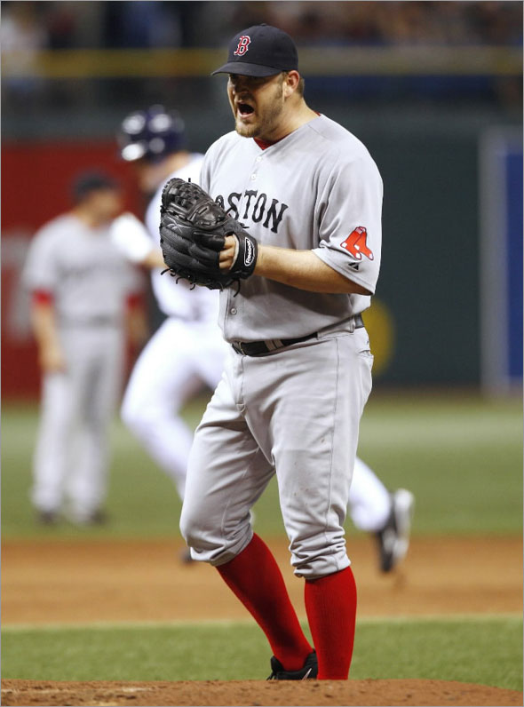 Red Sox pitcher Brad Penny reacts to giving up a home run to the Tampa Bay Rays' Pat Burrell (background) during the sixth inning their MLB American League baseball game in St. Petersburg, Florida August 5, 2009.