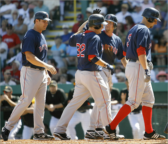 Boston Red Sox' Brad Wilkerson is greeted by teammates Jed Lowrie, Josh Bard, right, and Jeff Bailey,left, after driving them in after hitting a grand-slam home run against the Pittsburgh Pirates in the third inning of the spring training baseball game in Bradenton, Fla., Monday, March 9, 2009.
