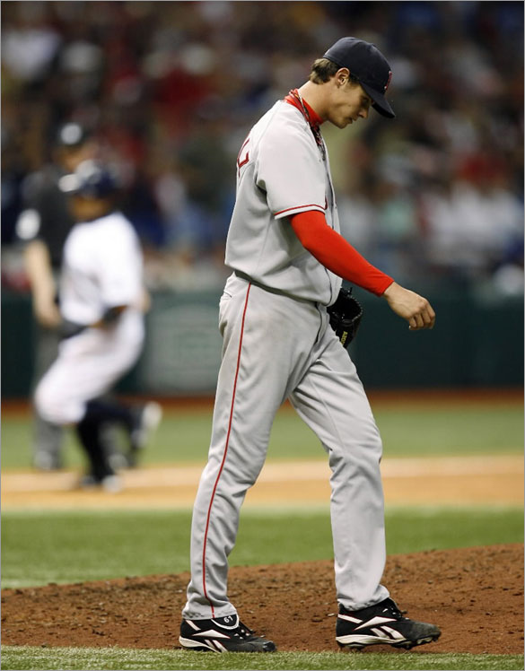 Red Sox starting pitcher Clay Buchholz returns to the mound after giving up an eighth-inning, two-run home run to Tampa Bay Rays' Akinori Iwamura, rounding the bases in the background, during a baseball game Saturday, April 26, 2008, in St. Petersburg, Fla. The Rays won 2-1.