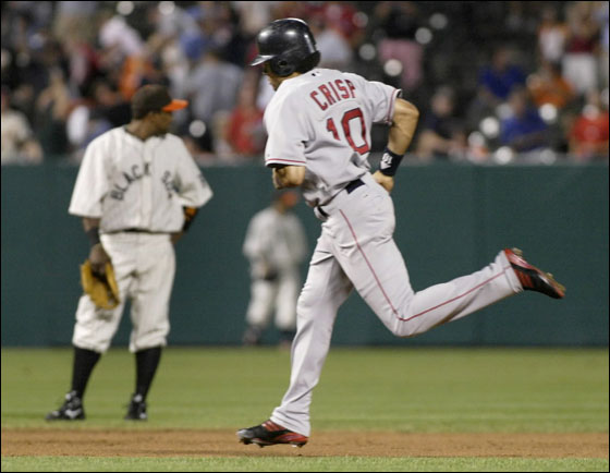 Red Sox base runner Coco Crisp rounds the bases past Baltimore Orioles shortstop Miguel Tejada after hitting a three-run home run off Baltimore Orioles starting pitcher Garrett Olson in the fourth inning of their MLB American League baseball game in Baltimore