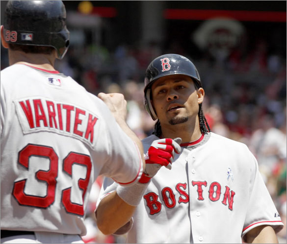 Coco Crisp, right, is congratulated by teammate Jason Varitek, left, after Crisp hit a two-run home run off Cincinnati Reds pitcher Homer Bailey in the second inning of a baseball game, Sunday, June 15, 2008, in Cincinnati.