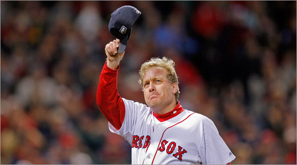An emotional Red Sox starting pitcher Curt Schilling tips his cap to the crowd (perhaps for the last time in Boston) as he leaves the game in the sixth inning.