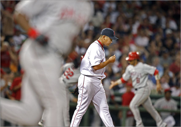 Red Sox pitcher Daisuke Matsuzaka is caught in the middle as the Angels Torii Hunter round first at left, and teammate Maicer Izturis rounds third at right following Hunter's sixth inning three rund home run that spelled the end of the Boston starter's night.
