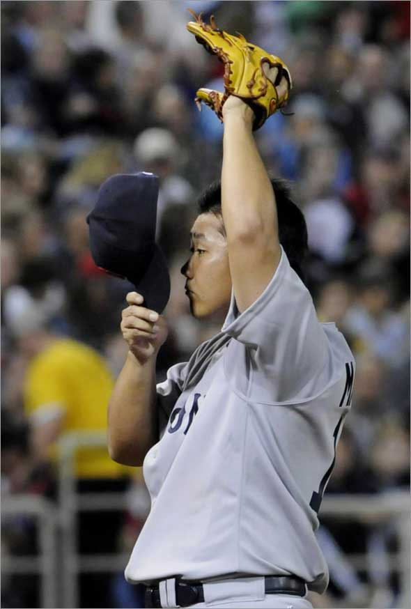Red Sox pitcher Daisuke Matsuzaka, of Japan, removes his cap momentarily after giving up the third run in the third inning to the Minnesota Twins in a baseball game Wednesday, May 27, 2009, in Minneapolis.
