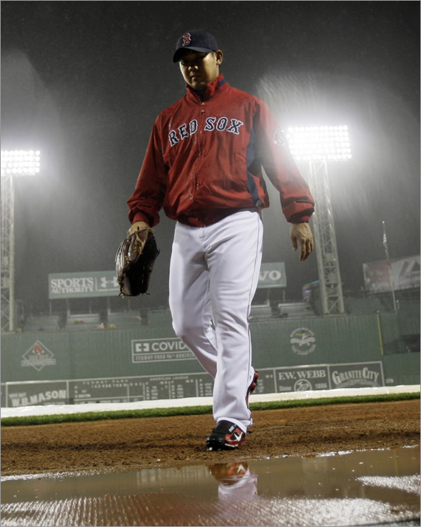 Red Sox pitcher Daisuke Matsuzaka walks into the dugout at Fenway Park after he was scratched as the starting pitcher in their baseball game against the New York Yankees due to the game's delay and the rainy weather in Boston Friday, Sept. 26, 2008