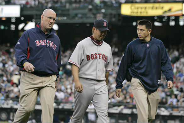 Red Sox pitcher Daisuke Matsuzaka, center, walks off the field with a trainer, left, and his interpreter as he leaves the game at the start of the fifth inning against the Seattle Mariners in their baseball game in Seattle, Tuesday, May 27, 2008