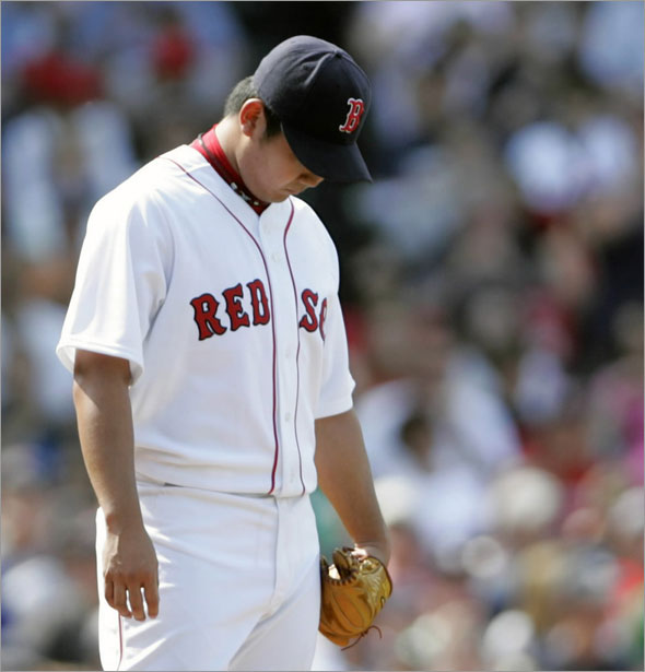 Red Sox starting pitcher Daisuke Matsuzaka of Japan hangs his head as he is taken out of the game against the Texas Rangers during the sixth inning of their American League MLB baseball game at Fenway Park in Boston, Massachusetts June 7, 2009.