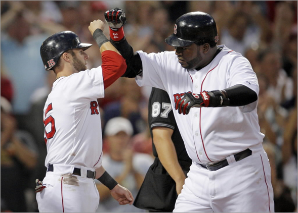 David Ortiz, right, is welcomed home by Dustin Pedroia after Ortiz hit a three-run home run off Texas Rangers' Tommy Hunter in the second inning inning of a baseball game at Fenway Park, in Boston, Thursday, Aug. 14, 2008. The Red Sox won 10-0.