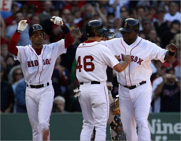 Red Sox DH David Ortiz is greeted at home by Julio Lugo and Jacoby Ellsbury after his 3 run homer in the 2nd.