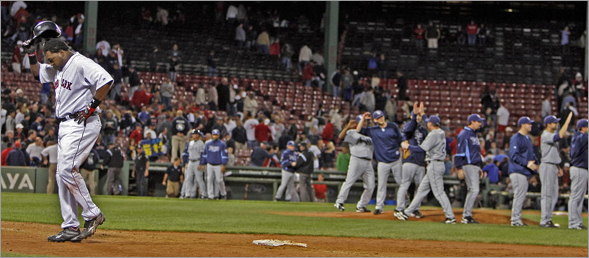 The Rays (right) celebrate and David Ortiz (left) doesn't after the last out of the game.