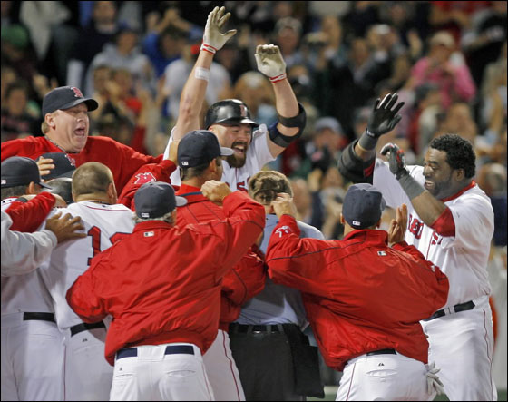 David Ortiz, right, is welcomed home by teammates after hitting a two-run home run off a pitch by Al Reyes in the ninth inning at Fenway Park, Wednesday, Sept. 12, 2007. The two-run home run gave the Red Sox a come from behind win