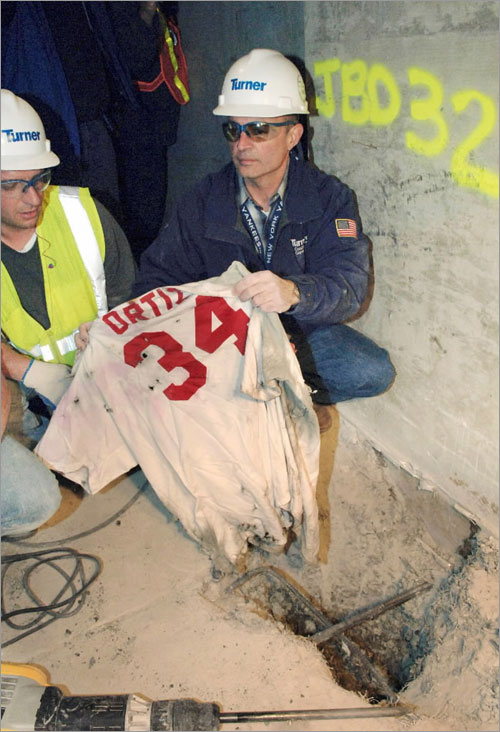 Frank Gramarossa, project executive for the new Yankee Stadium, removes a Boston Red Sox jersey with the name of player David Ortiz from the ground at the new Yankee Stadium in New York, Sunday, April 13, 2008.