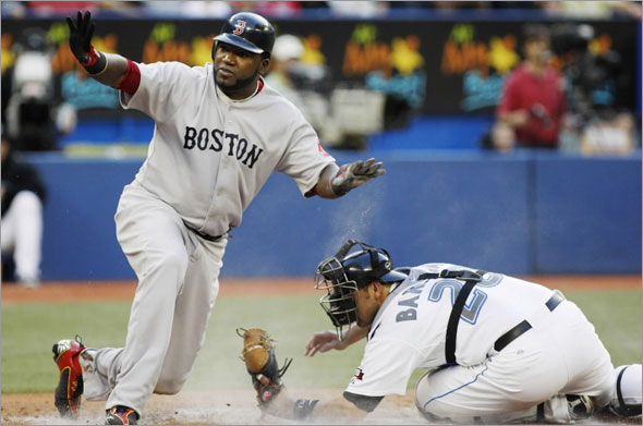 Red Sox David Ortiz waves safe after sliding into home safely as Toronto Blue Jays Rod Barajas tries to tag him during the second inning of their MLB American League baseball game in Toronto August 18, 2009.