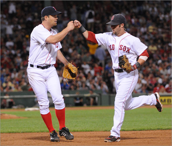 Red Sox starting pitcher Paul Byrd gives a fist hit to teammate second baseman Dustin Pedroia during the 6th inning. The Boston Red Sox host the Baltimore Orioles in a MLB game played at Fenway Park in Boston, MA Monday, September 1, 2008.