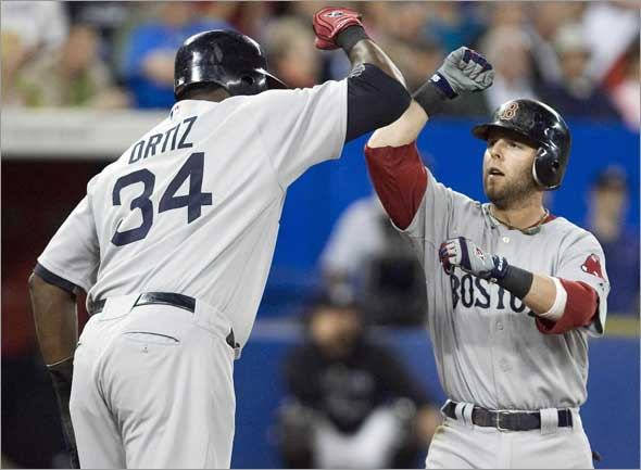 Red Sox second baseman Dustin Pedroia is congratulated by team mate David Ortiz after hitting a three-run home run against Toronto Blue Jays in the fourth inning