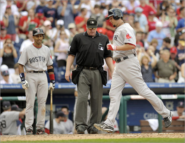 Red Sox starting pitcher Josh Beckett steps on home plate as umpire Brian Runge  looks on after he hit a solo home run off Philadelphia Phillies pitcher J.A. Happ  in the seventh inning