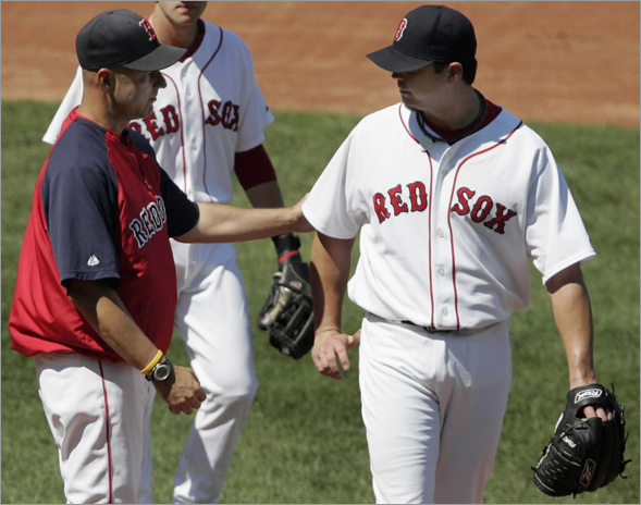 Terry Francona (left) pats Boston Red Sox starting pitcher Josh Beckett on the back as he is taken out of the game during the third inning against the Toronto Blue Jays