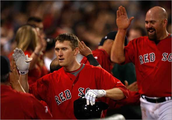 Boston Red Sox left fielder Jason Bay is congratulated in the dugout after his 2 run HR off New York Yankees relief pitcher Mariano Rivera (42), not pictured, tied the game at 4-4 in the 9th.