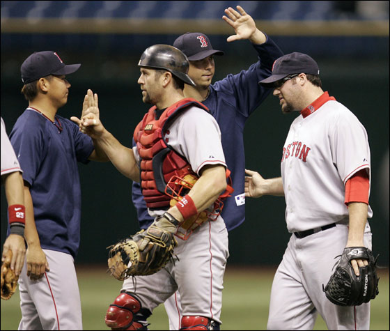 Red Sox pitcher Eric Gagne, right, and catcher Jason Varitek, second from left, gets high-fives from teammates Hideki Okajima, left, of Japan, and Josh Beckett, second from right, after the Red Sox defeated the Tampa Bay Devil Rays, 8-1, during a baseball game Friday night Sept. 21, 2007, in St. Petersburg, Fla. Beckett won his 20th game of the season