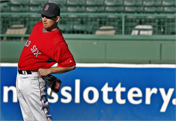 J.D. Drew is shown here stretching his back while shagging in the outfield during batting practice before Tuesday night's playoff clinching game at Fenway Park vs. the Indians.