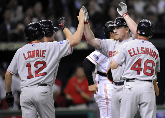 Boston Red Sox J.D. Drew is congratulated by team mates after he blast a grand slam home run during the sixth inning of their exhibition baseball game against the Yomiuri Giants in Tokyo March 23, 2008.