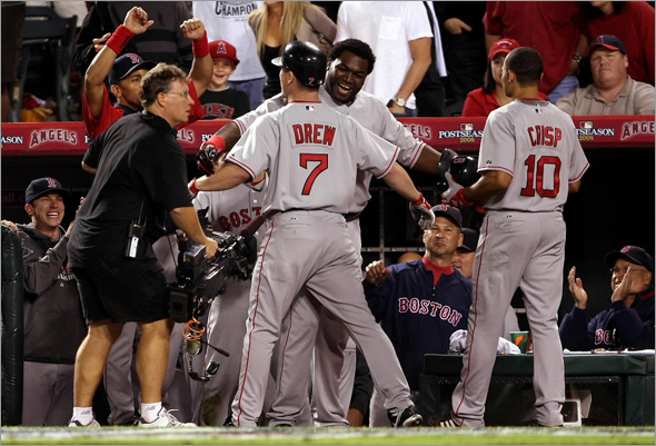 J.D. Drew of the Boston Red Sox celebrates with teammate David Ortiz No. 34 after hitting a two run home run in the ninth inning of game two of the American League Division Series against the Los Angeles Angels of Anaheim at Angel Stadium on October 3, 2008 in Anaheim, California