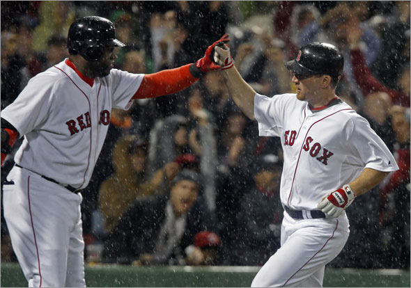 Yankees reliever Alfredo Aceves (backround left), gets a god view as Red Sox DH David Ortiz (center) gives a hand to teammate J.D. Drew (right) as he scores the winning run of the game on a bottom of the eighth inning on a sacrifice fly by Mike Lowell