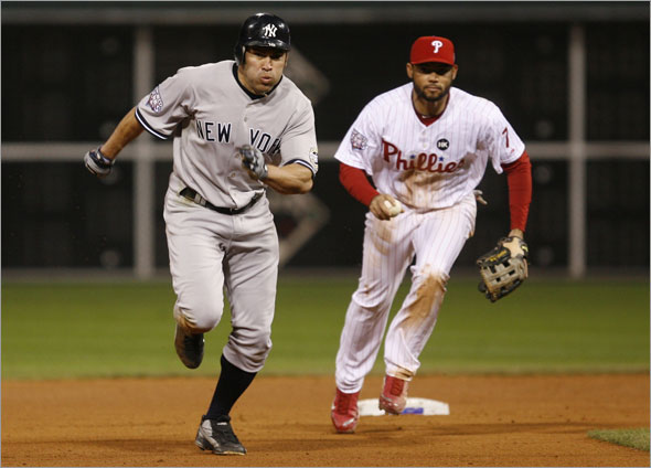 Johnny Damon runs to third base chased down by Philadelphia Phillies Pedro Feliz during the ninth inning in Game 4 of the 2009 Major League Baseball World Series in Philadelphia, November 1, 2009