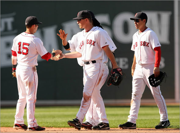 Dustin Pedroia is congratulated by teammates J.D. Drew, Jacoby Ellsbury  and Manny Ramirez after Pedroia made the catch for the final out of the game on July 13, 2008 at Fenway Park in Boston, Massachusetts.