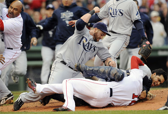 Tampa Bay Rays DH Jonny Gomes cocks his arm as Rays catcher Dioner Navarro  holds Red Sox center fielder Coco Crisp on the ground and in a head lock during the second inning.