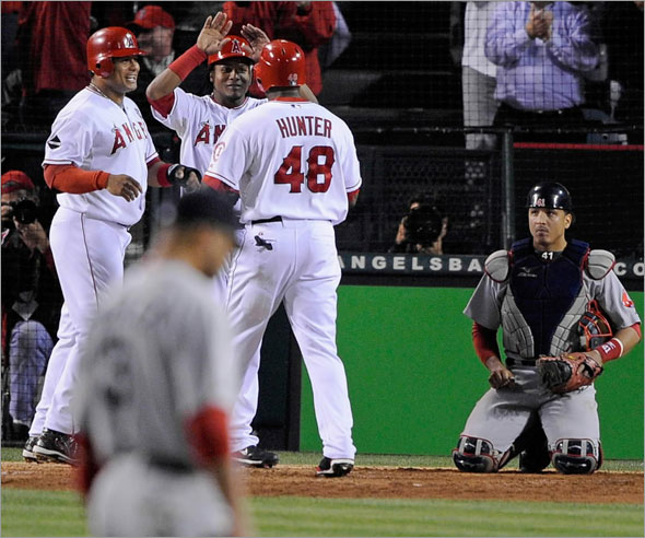 Torii Hunter of the Los Angeles Angels of Anaheim celebrates with teammates after hitting a three-run home run as starting pitcher Jon Lester #31 and catcher Victor Martinez #41 of the Boston Red Sox look on in the fifth inning of Game One of the ALDS during the 2009 MLB Playoffs at Angel Stadium