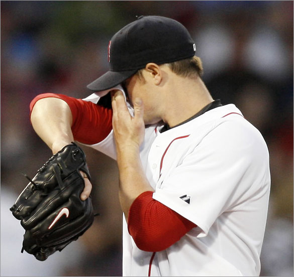 Red Sox pitcher Jon Lester wipes his face after giving up an RBI single during the third inning against the Los Angeles Angels in a baseball game at Fenway Park in Boston Wednesday, April 23, 2008. Lester gave up nine hits and four runs over five innings.