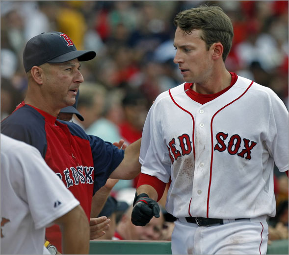 Red Sox manager Terry Francona (left) who had some praise for SS Jed Lowrie (right) during his post game press conference, gives him a hand as he comes into the dugout after scoring in the fourth inning.