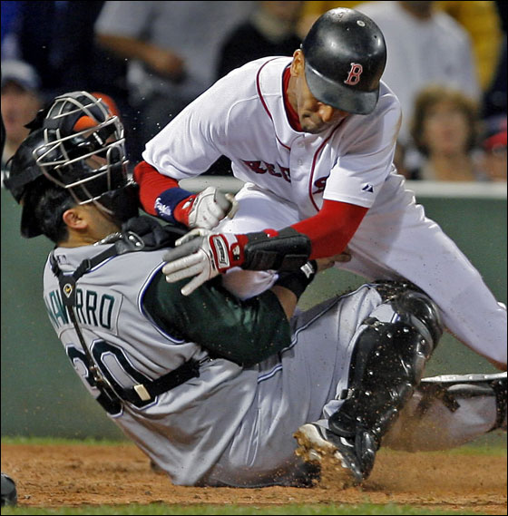 The Red Sox' Julio Lugo slams into Tampa Bay catcher Dioner Navarro as he tags up and scores from third on a fourth inning sacrifice fly by Dustin Pedroia.