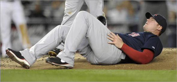Red Sox starting pitcher Jon Lester rolls on the mound after he was hit by a ball off the bat of New York Yankees batter Melky Cabrera in the third inning of their MLB American League baseball game at Yankee Stadium in New York