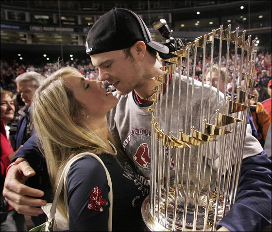 Winning pitcher Jon Lester kisses his girlfriend Farah Johnson as he holds the World Series trophy.