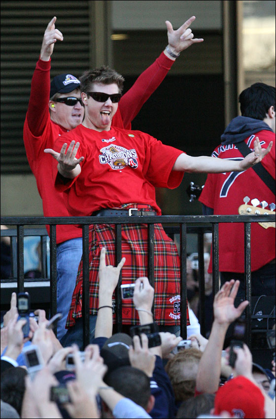 Boston Red Sox players Jonathan Papelbon (foreground, right) and Mike Timlin (behind left) celebrate the team's World Series championship on flatbed truck as rolling rally passes Boston City Hall.