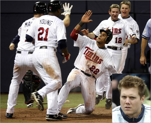 Minnesota Twins Carlos Gomez (22) slides safely into home, and celebrates with teammates Joe Mauer (L), Delmon Young (21) and Adam Everett (12), with the game-winning run after scoring on a hit by teammate Mike Lamb off Red Sox relief pitcher Jonathan Papelbon during the ninth inning